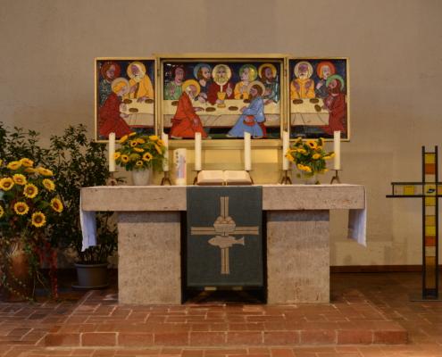Geschmückter Altar mit angezündeten Kerzen und geöffnetem Altarbild