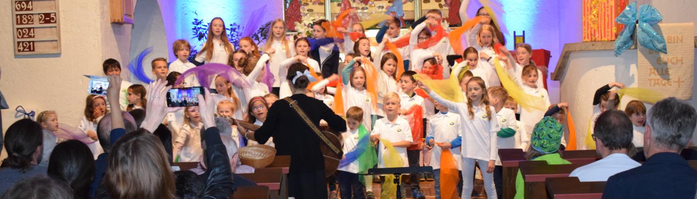 Kinder der Kinderchores schwingen bunte Tücher bei einer Aufführung in der Kirche