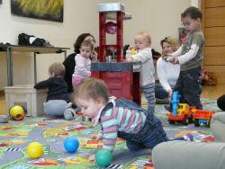 Kinder spielen mit eine Spielküche und ein Kind krabbelt einem Ball hinterher.