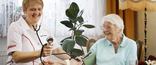 Pflegeschwester misst den Blutdruck bei einer Patientin