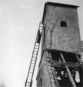 Turm der alten Marienkirche mit großen Rissen und einem Mann auf einer langen Leiter die an dem Turm lehnt.