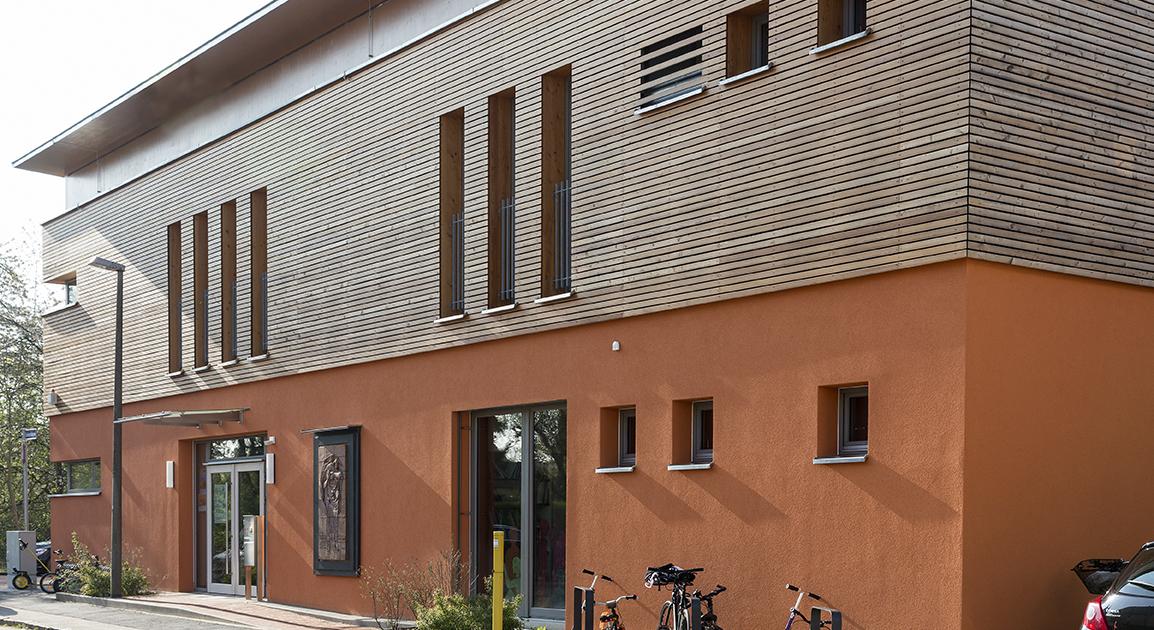 Frontansicht der Kindertagesstätte, ein oranges Haus mit Holzverkleidung im oberen Stockwerk und vielen bodentiefen Glasfenstern.