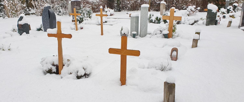 Grabsteine und Kreuze auf dem Friedhof. Bedeckt mit Schnee.