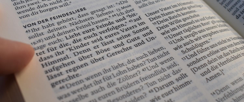 Finger deutet auf Text in einer aufgeschlagenen Bibel