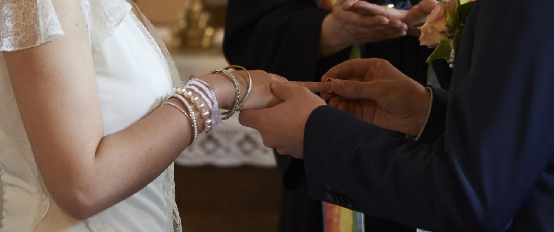 Bräutigam steckt der Braut den Ring an den Finger.
